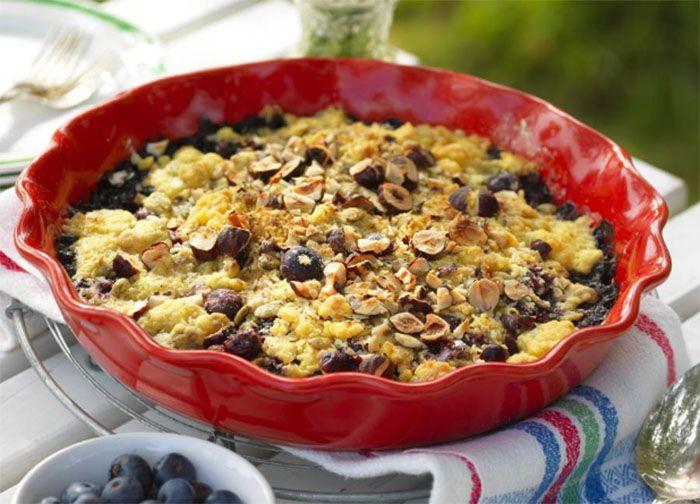 En smulpaj med det lilla extra! Fyll en pajform med blåbär, kokos och nötter.