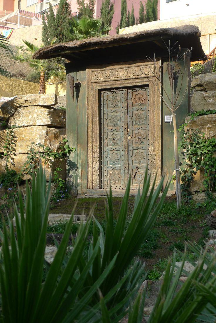 Reforma en jardín. Puerta rústica de entrada trasera a parcela en vivienda, madera maciza ornamentada y cubierta de brezo. #jardín #reforma #puerta #rustico #madera #coberti