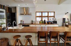 キッチンの大きなカウンターテーブルの天板は、一枚板をアンティーク風に加工したもの。ブロックを積んだものの上に載せられている。