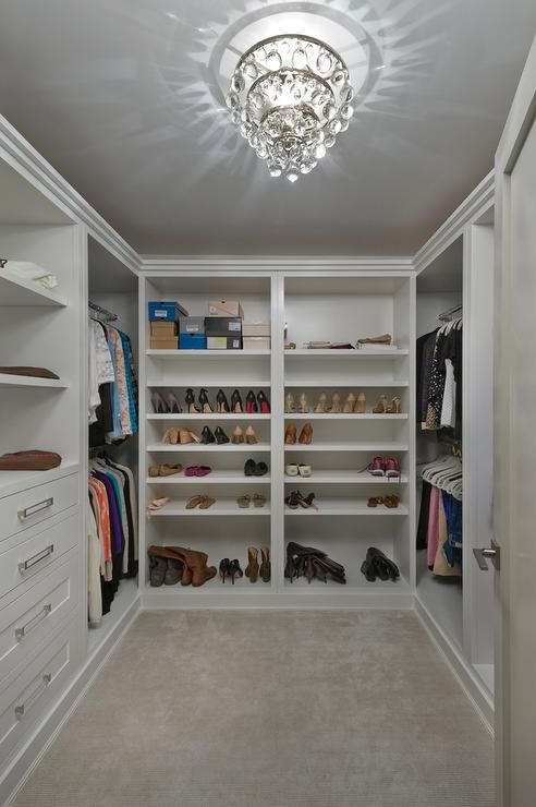 White walk-in closet features built in shelving and stacked clothes rails as well as a built in dresser illuminated by a Robert Abbey Bling Semi Flushmount.