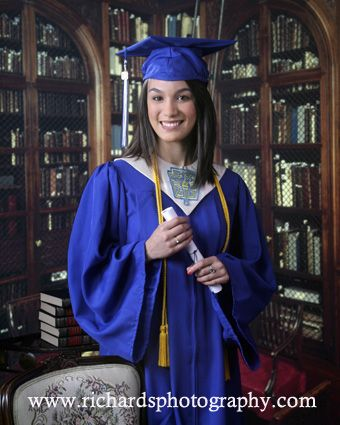 Blue cap and gown with bookcase background