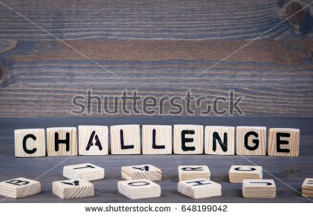 Challenge word written on wood block. Dark wood background with texture.