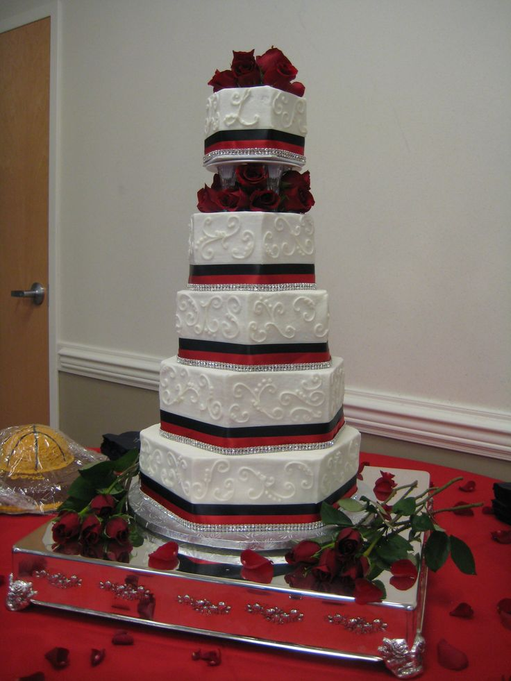 Five tier hexagon wedding cake stacked with corners offset. Decorated with scrollwork, double ribbon, rhinestones, fresh roses, red and black ribbons.
