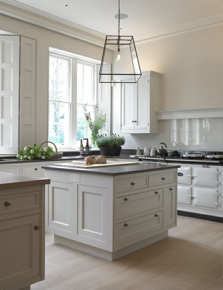 Definitely need a center island in the kitchen.  nice white cabinets with slate counter tops and white backsplash. can we talk about this iron chandelier with an antique bulb? love this.