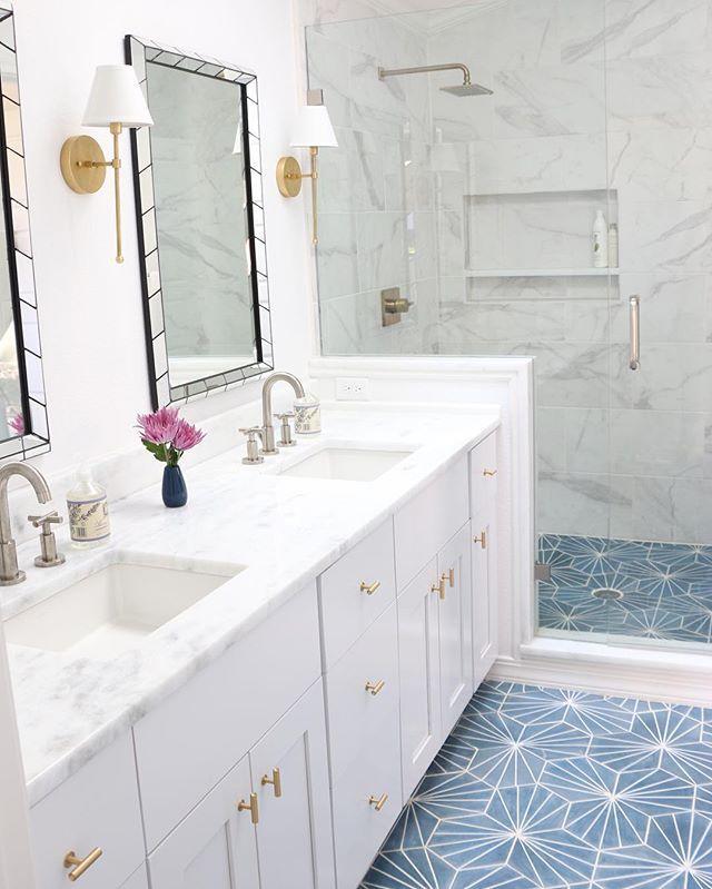 O piso azul e branco deste banheiro quebra e ao mesmo tempo harmoniza com os móveis e revestimento branco e detalhes em dourado. A mármore branca adiciona requinte à decoração.