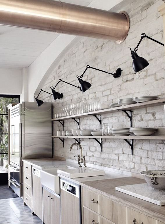 pale wood cabinets + brick wall + wood countertops + line of arm lights (how did they wire these?)