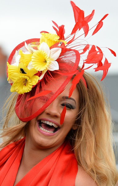 A racegoer poses for photographers as they attend Ladies Day, the second day of the Grand National Meeting horse racing event at Aintree Racecourse in Liverpool, north-west England on April 5, 2013. The annual three day meeting culminates in the Grand National which is run over a distance of four miles and four furlongs (7,242 metres), and is the biggest betting race in the United Kingdom. ANDREW YATES/AFP/Getty Images