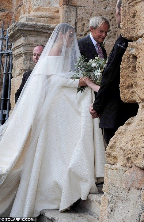 Elegant. Smiling as she approached the church, with her veil pulled down over her face, Lady Charlotte took a quiet moment (left) before entering
