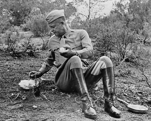 World War II, Future President General Dwight D. Eisenhower (1890-1969), stopping for noon mess by the roadside during an inspection tour in Tunisia. The menu is a C ration, and hot. It was kept warm by being packed next to the manifold of the General's car enroute, photograph, 1943.