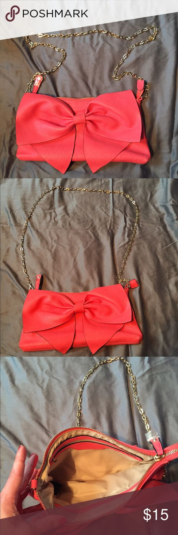 "Coral Bow Handbag Beautiful Coral Bow bag. Purchased from Just Fav a couple years ago but I never ended up wearing it. Still has the plastic on the zipper pull. It has two smaller pockets on the inside and one larger pocket that has a zipper. 12"" inches across and 6"" inches in height. Beautiful gold chain that's also removable if you wanted to wear this bag as a clutch! Priced to sell. Price is firm. It's so gorgeous and versatile! Perfect for summer! 😍 JustFab Bags"