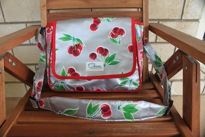 A school bag for a very special young girl. It's made with silver oilcloth with big red cherries on it. Absolutely adorable!