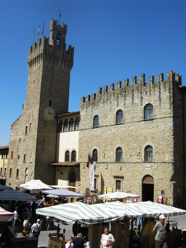 Arezzo, the beautiful Town Hall palace with medieval tower and the booths of the Antique Market below