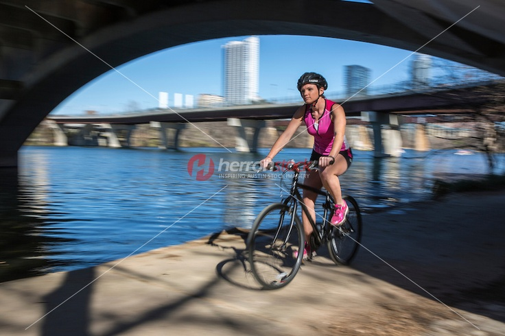 Young Woman athlete speeding down the trail on the Lady Bird Lake Hike and Bike Trail on Town Lake Austin (intentional motion blur).