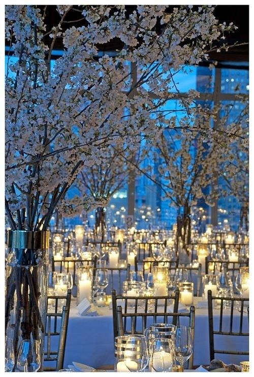 Use candles to light up your venue with white blossomed branches, lovely for a white winter wedding.