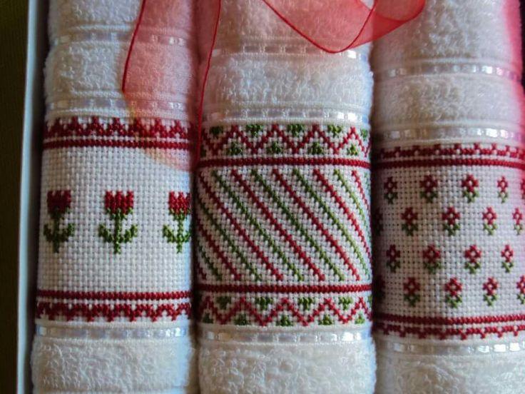 Juego de 3 toallas pequeñas con bordados en punto cruz de flores y geométricos en rojo y verde.