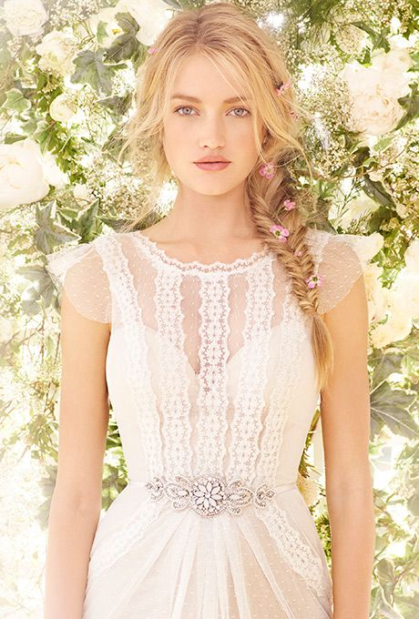 """Brides: Ti Adora by Alvina Valenta. Ivory / Cashmere point d'esprit gown. Sheer bateau neckline with open """"v"""" back and cap sleeve with intricate embroidered lace throughout bodice and detachable satin ribbon belt with jeweled applique at the natural waist."""