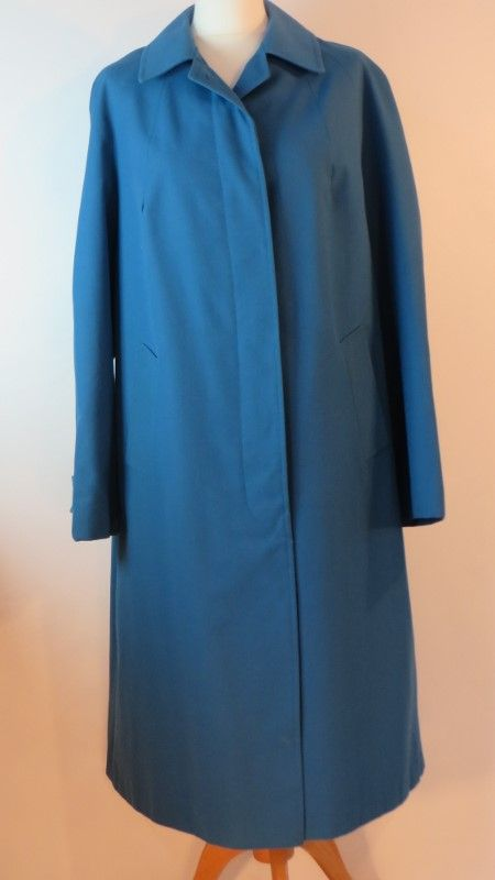 Vintage blue Dannimac rain coat, 20.   Charming 1970s teal blue Dannimac rain coat, fully lined.     Size: 20 Measurements: B: 46, W: 48, H: 49, L: 42, S-S: 18, A: 16.5 Label: Dannimac Decade: 1970 Material: Trevira (polyester / nylon)  Cleaning instructions: Machine wash at 30 degrees with a silk / wool liquid / dry clean