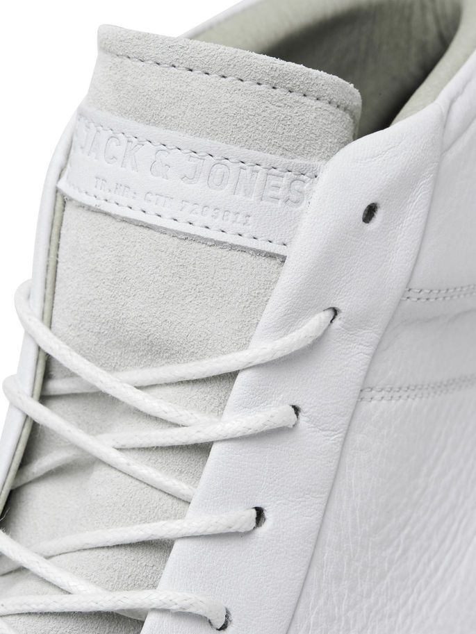 White mid-cut leather sneakers are a must-have item for your wardrobe. Style them with a pair of blue denim jeans, cargo pants or chinos. With soft microfiber lining for added breathability | JACK & JONES #footwear #trainers #leather #luxe #menswear #menstyle