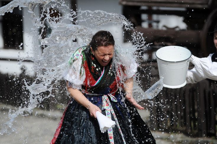 "A Hungarian girl dressed in traditional garb is soaked by local boys in the main street of the village of Holloko, about 100 kms northeast of Budapest. Holloko, a World Heritage site, will celebrate Easter next weekend with the traditional ""watering of girls,"" a fertility ritual rooted in Hungarian tribes of pre-Christian past, going as far back as the second century AD. (AFP)"
