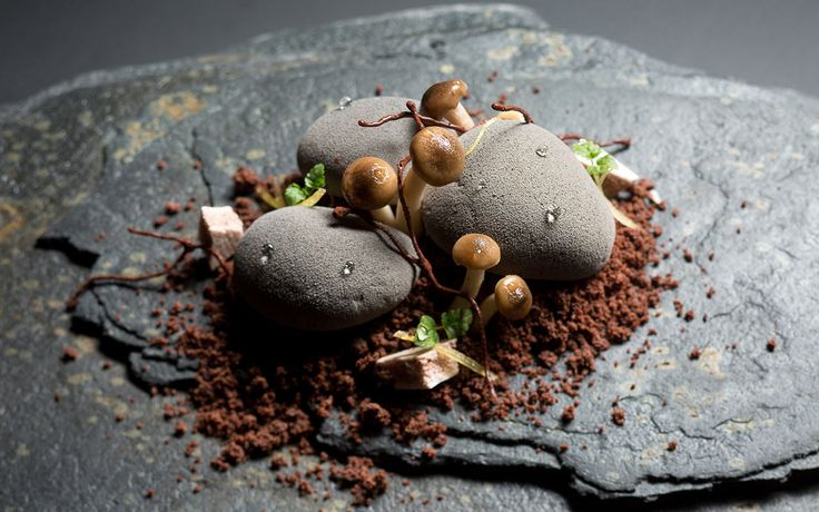 """COCOA PEBBLE DESSERT. Alpaco chocolate mousse """"stones"""" topped with meringue mushrooms and served on a sprinkling of chocolate soil. A hidden spoonful of lemon curd is ensconced within each pebble, acting as a brightness to lift the rich flavors."""