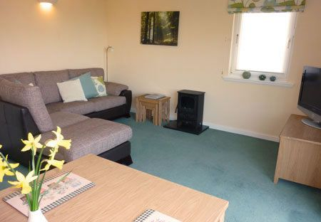 The lounge and dining area in Woodlea - Self Catering Cottage on the beautiful lsle of Arran, Scotland. This room ahs large sliding doors onto a sun deck overlooking the garden and Goatfell