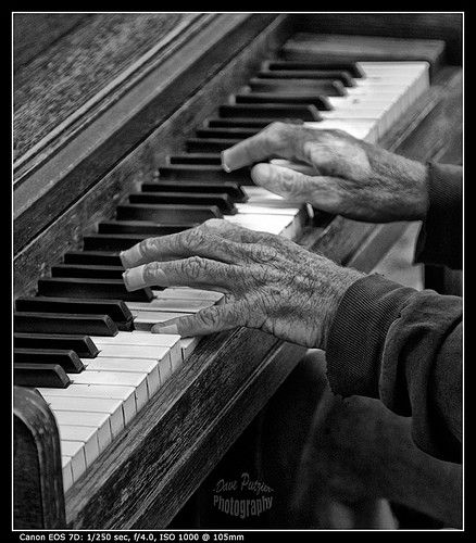 "Playing Through the Pain. Photo by David Putzier, Oregon Country Fair 2011. ""This old man was playing a rickety piano off the side of a path beautifully. He had bandages on most of his fingertips."""