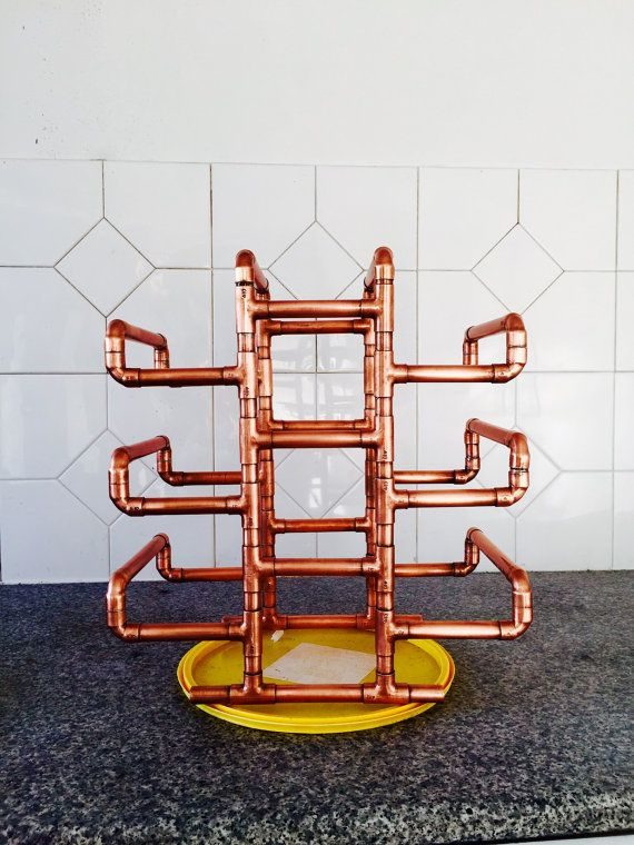 Here we have a lovely copper wine rack that holds up to 10 bottles of wine. It is handmade from copper pipe and finished with a lacquer coating to keep the shine. Will look good in any household/ restaurant or bar. Dimentions: H-40cm, W-20cm, L-35cm