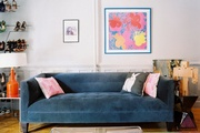 A gray velvet sofa surrounded by art objects