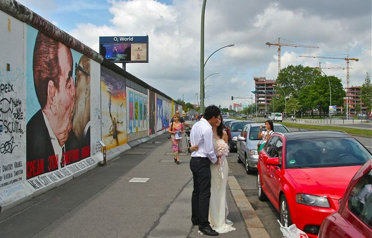 Just married couple posing in the front of Berlin wall and the painting of kissing Leonid Brezhnev and Erich Honecker. © Miikka Järvinen