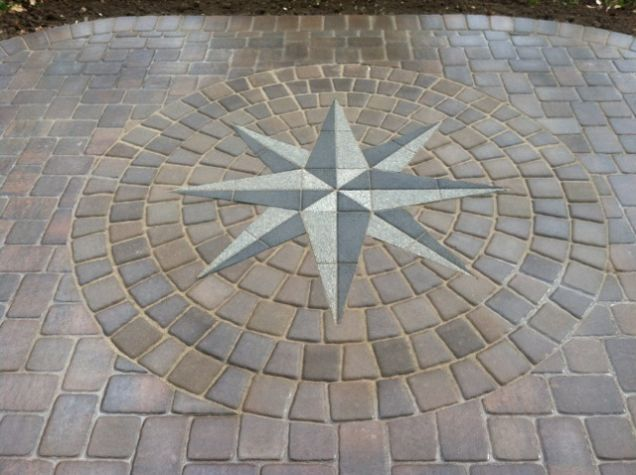 This project design consisted of a patio walk and 2 steps to replace the old worn out concrete pad that was existing. The patio created a nice sized entertaining area perfect for the clients needs. The custom inlaid compass rose was a great idea in the beginning and ended up being a beautiful, custom touch for this project.
