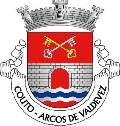 """Civic heraldry of Portugal - Brasões dos municípios Portugueses - Escudo de vermelho, ponte de um arco de prata, lavrada de negro, movente dos flancos e de um ondeado de prata e azul de três tiras; em chefe, duas chaves passadas em aspa, uma de ouro e outra de prata. Coroa mural de prata de três torres. Listel branco, com a legenda a negro em maiúsculas : Â""""COUTO – ARCOS DE VALDEVEZÂ""""."""