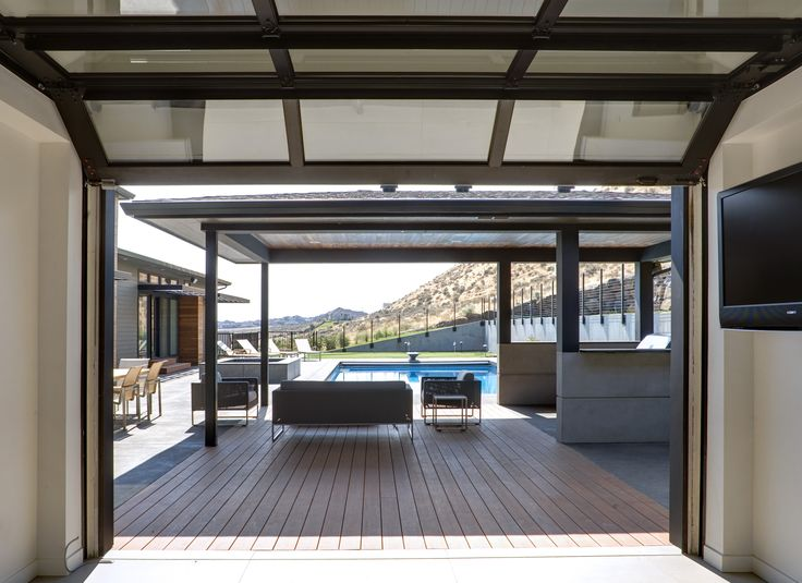 Garage door opening up to the pool cabana designed by First Lamp Architecture and Construction