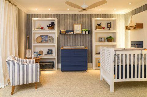 Inspirado no tema praia, o dormitório para bebê é assinado pela arquiteta Andrezza Alencar. O papel de parede com tema náutico dialoga com os móveis na cor azul e demais elementos, como o berço e as prateleiras, em tons sóbrios. A decoração complementa o conceito de praia, como o barco na estante esquerda.