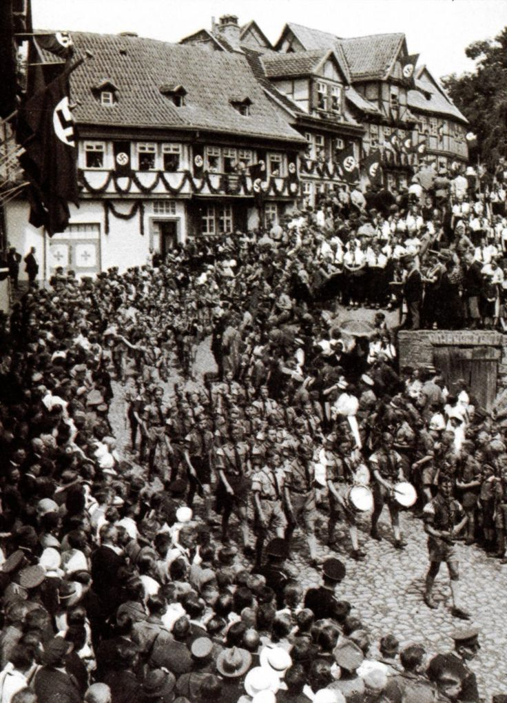 Enthusiasm for Hitler's regime was generated - for both internal and international audiences - by an endless schedule of public events. Here, Weimar turns out in July 1936 to cheer a youthful march through the cobblestone streets to celebrate the tenth anniversary of Nazi Party Day.