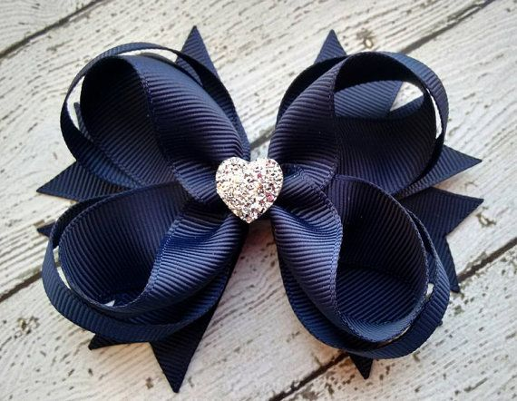 This Navy Boutique Girls Hair Bow with Sparkly Heart is very unique and carries a distinctive elegance and delicate charm. It is the perfect hair accessory for a wedding, party or any formal event. Your adorable little princesses will definitely look very endearing. They will love this as it is a fun and cute color. Add this to your collection of boutique bows or give as a cool and unique birthday or back to school gift.  This is made of 7/8 and 3/8 sized grosgrain ribbons that are heat…