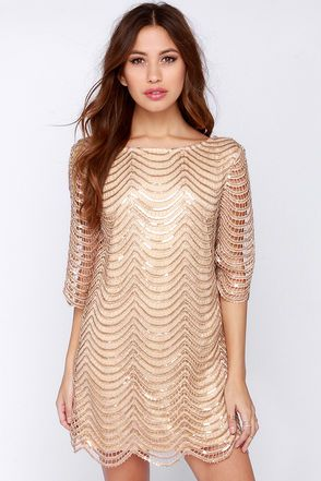 """Pop the champagne, because the Under the Affluence Beige Sequin Dress is intoxicating-ly beautiful! A network of sequin-embellished crochet scallops fall into tiers over a beige shift bodice, with a scoop neckline and low-dipping back. Sheer half sleeves bell out towards the elbows. Bodice is lined in beige stretch knit. Sleeves are sheer. Model is 5'7"""" and is wearing a size small. 100% Polyester. Dry Clean Only. Imported."""