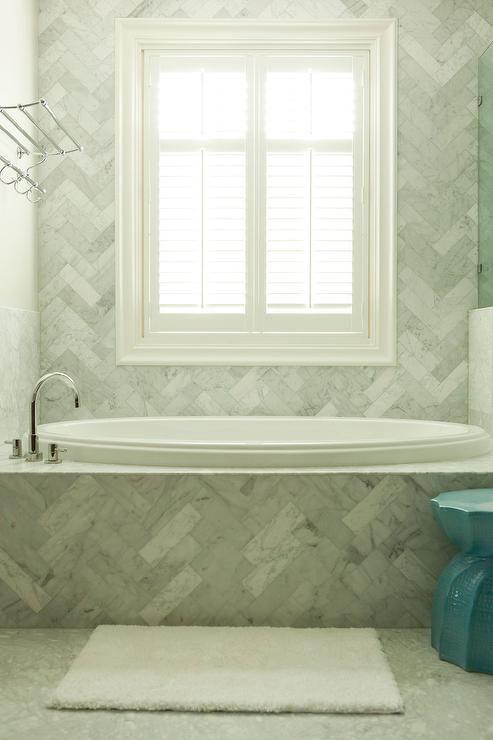 Stunning bathroom features a marble herringbone tiled tub alongside a marble herringbone surround ...