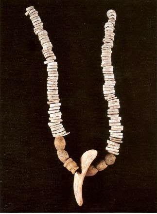Fig 24 Soleminis, Is Calitas, tomba I: collana composta da 31 rondelle di conchiglia consunta di forma ovale, un vago di conchiglia di forma triangolare, 5 vaghi a botticella in osso, 1 vago a tortue in osso, una placchetta tratta da una zanna di cinghiale con foro centrale. Cuccuru cresia arta Maria Rosaria Manunza Dolianova (Ca),Grafica del Parteolla 2005