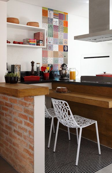 """Em um trecho da cozinha, o piso de porcelanato foi substituído por pastilhas de vidro pretas de 2 x 2 cm (Colormix). """"Queria um revestimento descontraído e também trazer charme para a área da bancada"""", explica a arquiteta Gisele.        modo slideshow"""