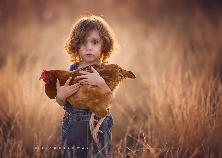 Photo à contre-jour d'un enfant tenant une poule