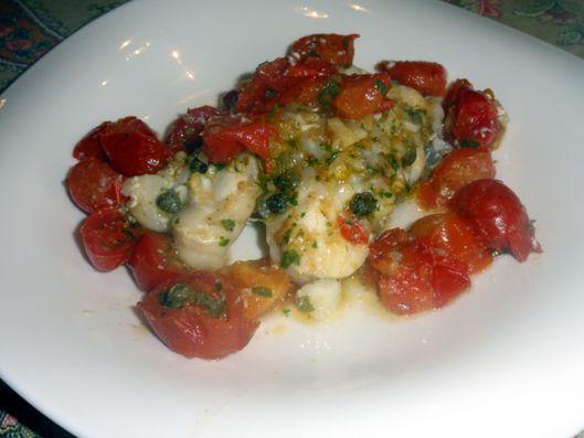 Tranci di coda di rospo aromatizzati cotti al forno con pomodorini e capperi