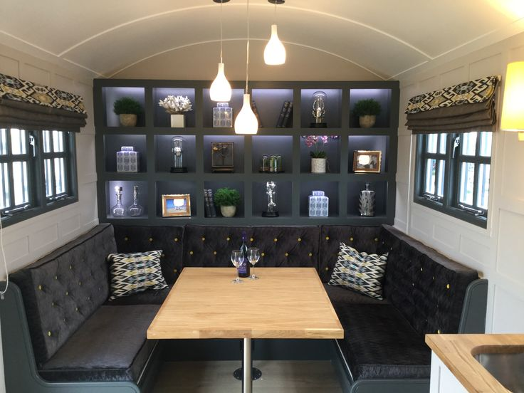 Design for Garden Hideouts shepherd hut by Bayswater Interiors. Feature storage, button-back banquette which converts to a bed, false pelmet roman blinds and pendant lighting and bespoke wall lights.