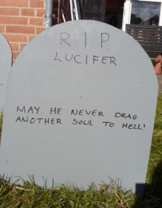Tombstone for Lucifer carved in wood and spraypainted grey.