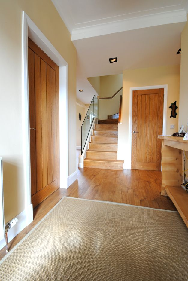 Hamilton Extension Design by Glasgow Architects, Allison Architecture. hallway with oak doors and oak staircase with frameless glass balustrade