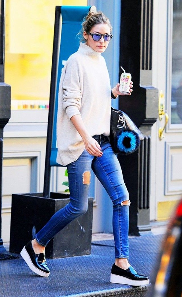 Olivia Palermo wears a turtleneck sweater, distressed skinny jeans, top-handle bag, platform sneakers, and mirrored sunglasses
