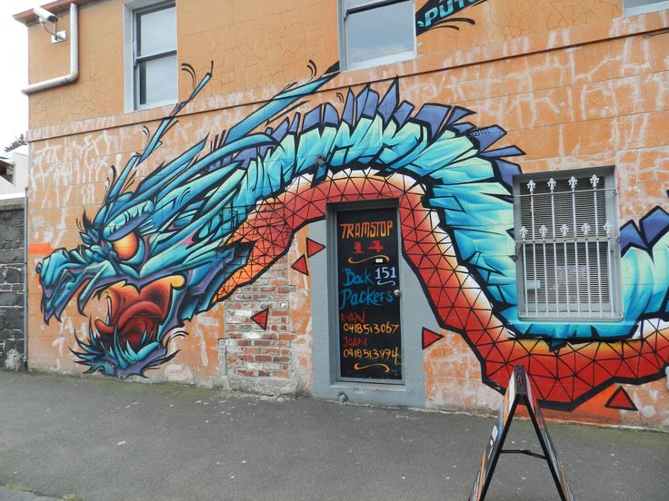 Dragon with tails wrapped around 2 sides, above backpackers lodge, Rose St Brunswick.