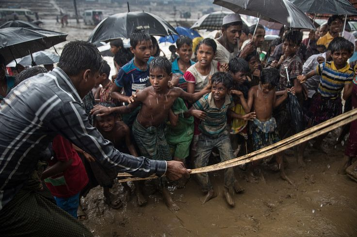A man strikes anxious Rohingya children with a cane as things get out of control during a humanitarian aid distribution while monsoon rains continue to batter the area causing more difficulties on October 7, 2017, in Thainkhali camp, Cox's Bazar. #  Paula Bronstein / Getty