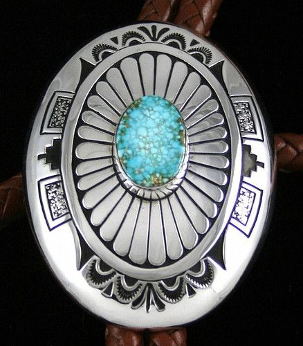Charlie John RARE High Grade Number Eight Spiderweb Turquoise Bolo Tie | eBay Navajo jeweler Charlie John has set an incredible rare high grade natural Number Eight spiderweb turquoise cabochon in this beautiful one of a kind bolo tie. The gem is light and dark blue with tight golden-brown and tan webbing and is from a mine that is no longer producing. Placed atop a domed sterling silver oval, the bolo has two layers of overlay.  $750