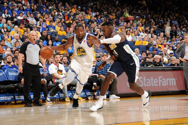 Kevin Durant of the Golden State Warriors drives to the basket against Paul Millsap of the Denver Nuggets during a preseason game on September 30...