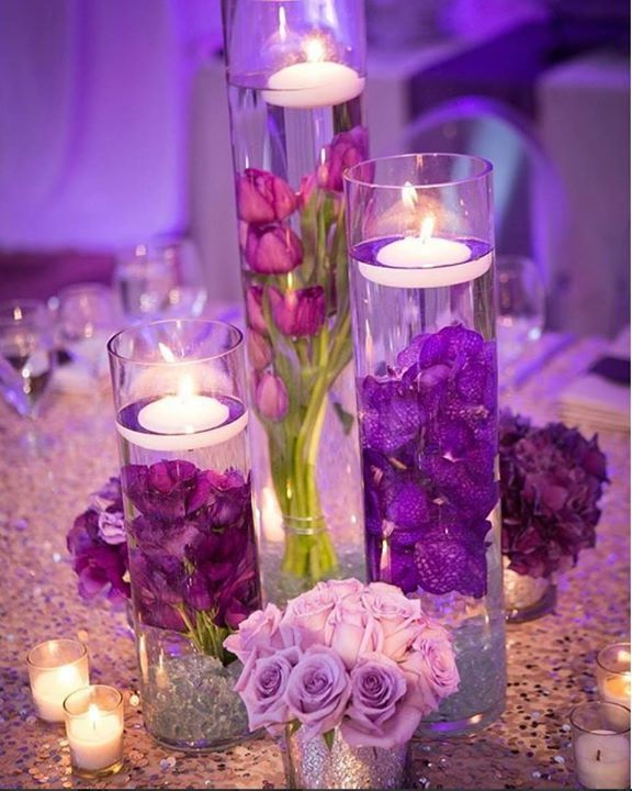 Centerpieces Of Candles Floating Over Submerged Purple Flowers On A Sequined Tablecloth Are Simple But